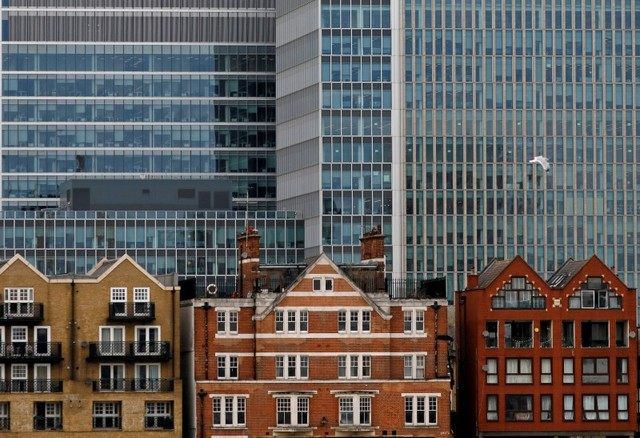 Apartment buildings are backdropped by skyscrapers of banks at Canary Wharf in London. Photo: Reuters/Reinhard Krause