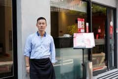 Chris Lee, a migrant from Hong Kong, poses at his restaurant in Taipei