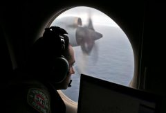 Flight officer Gharazeddine looks out of a RAAF AP-3C Orion as it flies over the southern Indian Ocean during the search for missing flight MH370