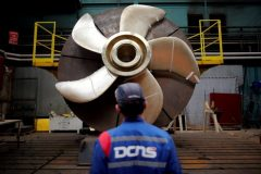 An employee looks at the propeller of a Scorpene submarine at the industrial site of the naval defence company and shipbuilder DCNS in La Montagne