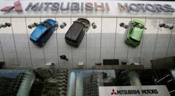 File photo of Mitsubishi Motors Corp's vehicles and a passer-by reflected on an external wall at the company headquarters in Tokyo