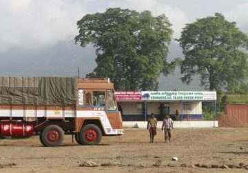 Truck drivers walk out of a Commercial Taxes Department check post after getting clearance to cross a checkpoint with their goods at the Chavadi checkpoint on outskirt of Coimbatore