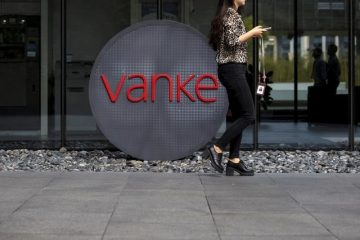 An employee walks past a logo of Vanke at its headquarters in Shenzhen, south China's Guangdong province, November 2, 2015. Reuters/Tyrone Siu/File Photo