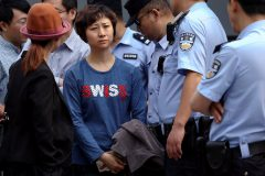Policemen stand next to Lin Ru, the wife of civil rights lawyer Xia Lin in Beijing