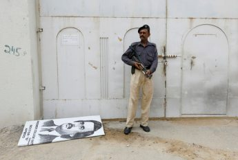 Policeman stands guard at an entrance gate with wax-sealed padlock, beside a poster depicting Altaf Hussain, leader of Muttahida Qaumi Movement (MQM) political party, after paramilitary forces sealed the headquarters in Karachi