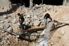 Men inspect a hole in the ground filled with water in a damaged site after airstrikes on the rebel held Tariq al-Bab neighbourhood of Aleppo