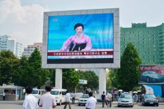 North Koreans walk past near a huge screen broadcasting the government's announcement on North Korea's fifth nuclear test in Pyongyang