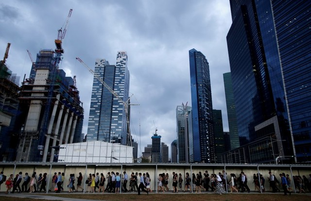 Office workers walk to the train station during evening rush hour in the financial district of Singapore March 9, 2015. Photo: Reuters/Edgar Su