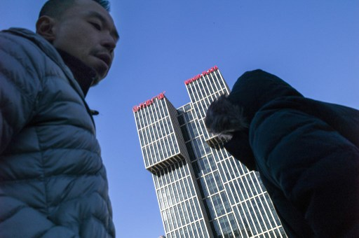 People walk along a road before the Chinese conglomerate Wanda Group building in Beijing. Photo: AFP/Fred Dufour