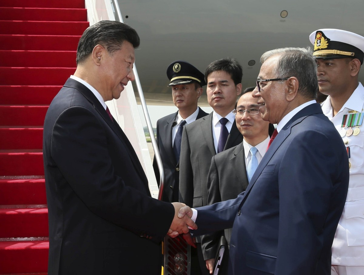 China's President Xi Jinping (L) shakes hands with his Bangladeshi counterpart Abdul Hamid after arriving in Dhaka on Friday.  Xinhua/via Reuters