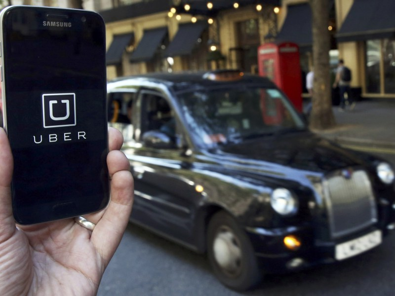 A photo illustration shows the Uber app logo displayed on a mobile telephone, as it is held up for a posed photograph in central London. Photo: REUTERS/Neil Hall