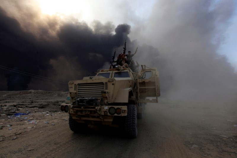 Iraqi military personnel ride on a military vehicle in Qayyarah, outside Mosul. Photo: REUTERS/Alaa Al-Marjani