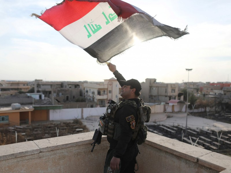 A special forces soldier waves an Iraqi flag from the top of a church damaged by ISIS forces in Bartella, east of Mosul, Iraq. Photo: Reuters/Goran Tomasevic