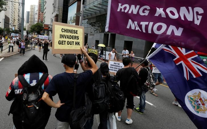 Pro-independence protesters carry placards and flags during a pro-democracy march. Photo: Reuters / Bobby Yip