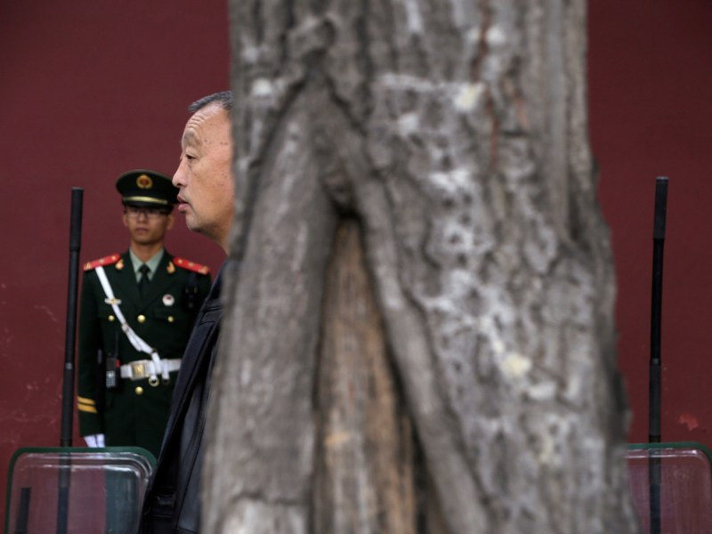 A man stands next to paramilitary police officers near Tiananmen Square during the 18th Central Committee of the Communist Party of China. Photo: REUTERS/Jason Lee