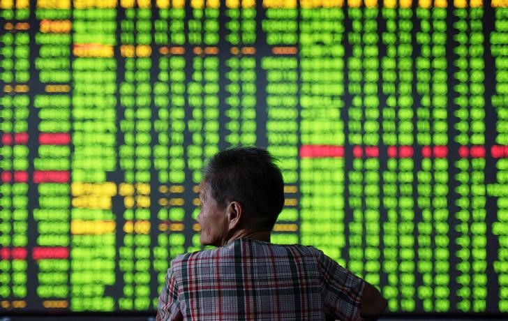 An investor is seen in front of an electronic screen showing stock information (green for losses) at a brokerage house in Hangzhou, Zhejiang Province, China. Photo: China Daily via Reuters