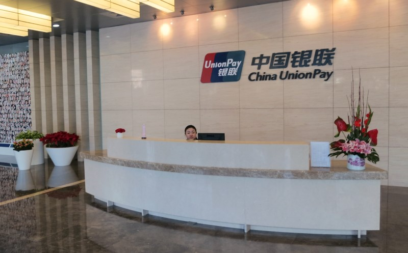 An employee sits behind a desk at the reception area of China UnionPay's headquarters in Shanghai. Photo: Reuters/James Pomfret