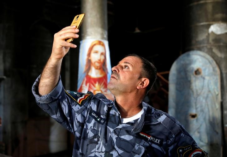 An Iraqi Christian police officer takes pictures during the first Sunday mass at the Grand Immaculate Church since it was recaptured from Islamic State in Qaraqosh, near Mosul in Iraq October 30, 2016. Photo: Reuters/Ahmed Jadallah