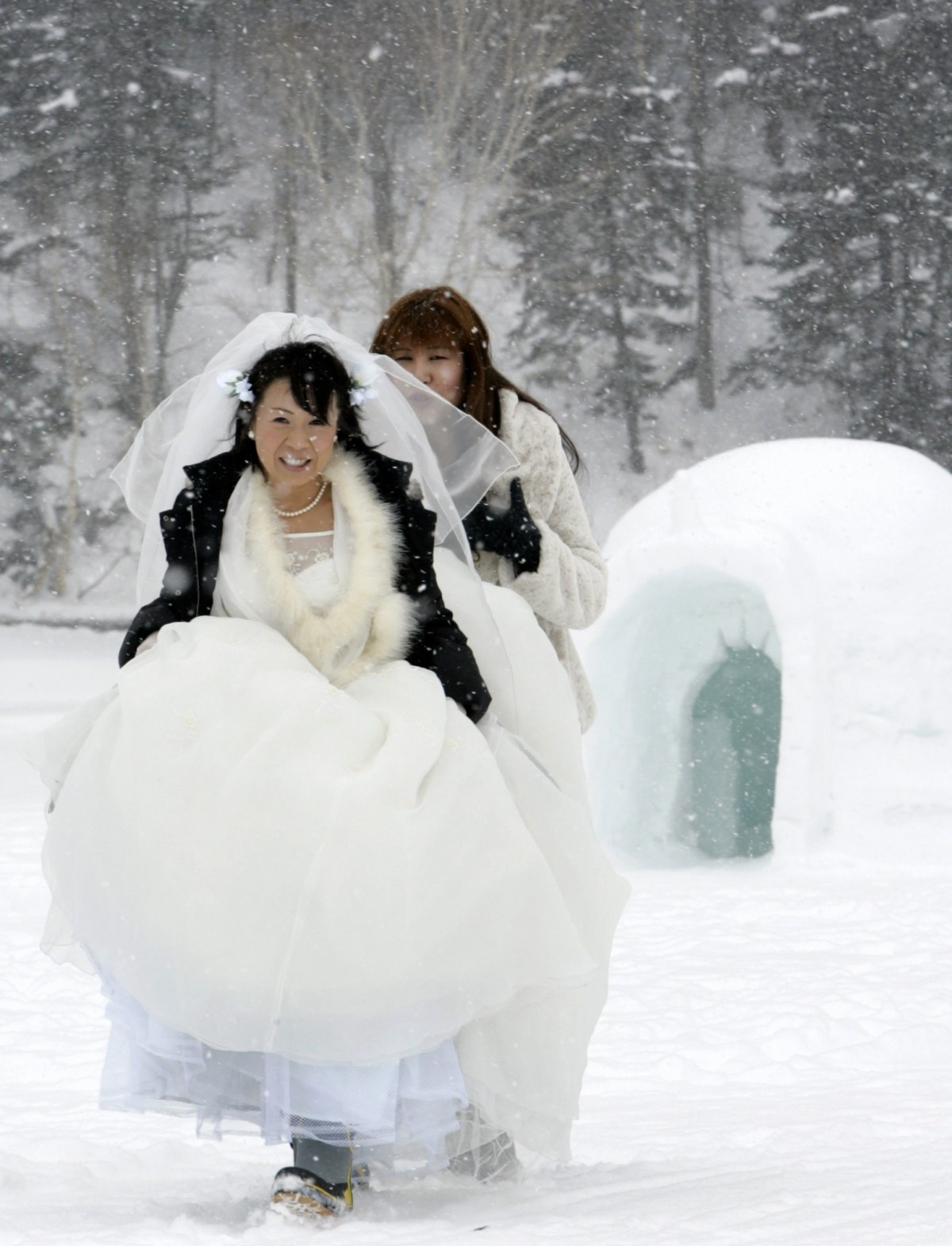 A bride braves the snow and cold as she walks towards her wedding ceremony at the 'Igloo village' on Lake Shikaribetsu in Shikaoi town in Japan's northern island of Hokkaido February 14, 2007. Reuters/Yuriko Nakao.