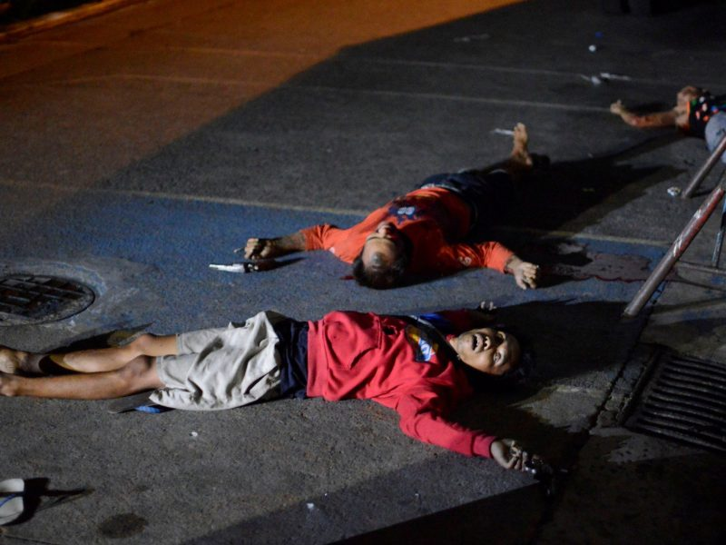 Three men who police said died in a shootout at a checkpoint, lie on the ground in Manila with guns near their hands Sept. 21, 2016. Photo by Ezra Acayan, Reuters.