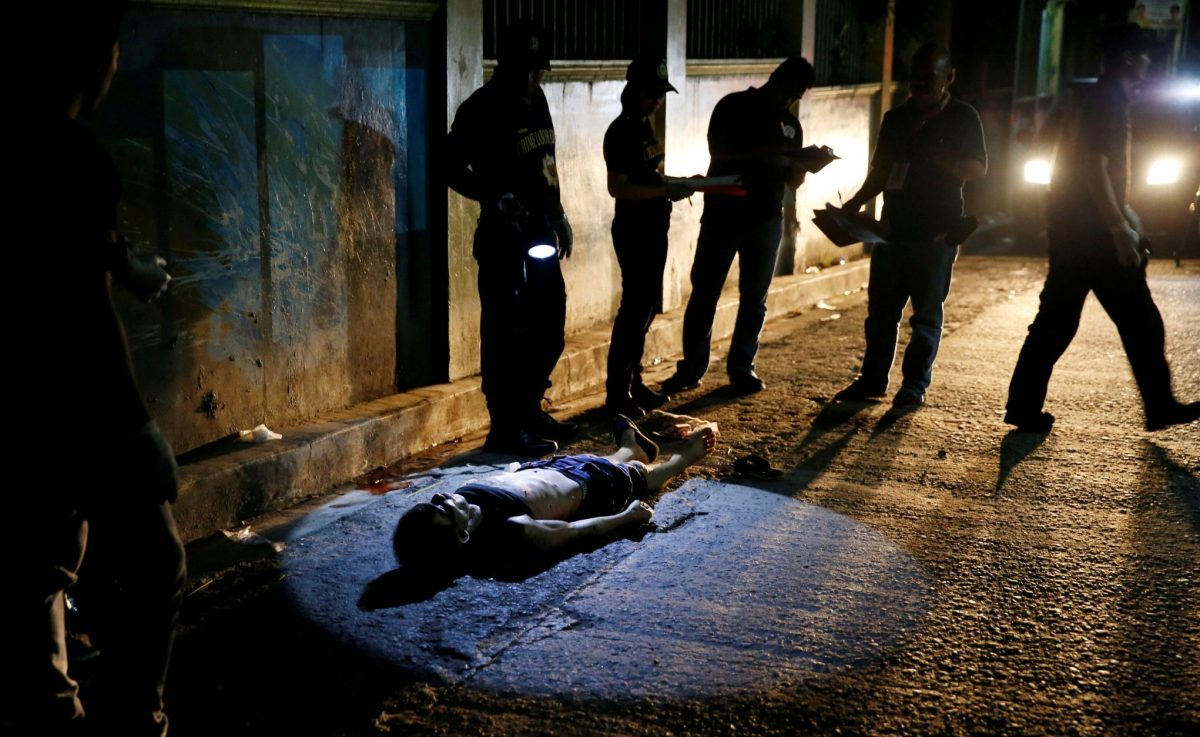 Police torches lights up the body of a suspected drug dealer, killed by two men on motorcycles in Quezon City, Manila. Photo: Reuters/Erik De Castro