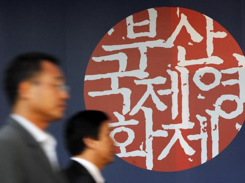People walk past the Busan International Film Festival logo. Photo: Reuters