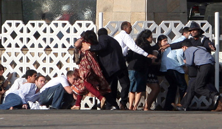 People duck as gunshots are fired from inside the Taj Mahal hotel in Mumbai November 27, 2008. Photo: Reuters/Punit Paranjpe