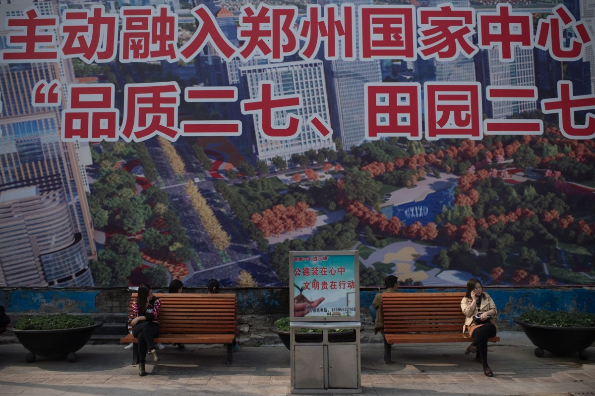 Women sit in front of a giant advert for a property development project in Zhengzhou. Photo: AFP