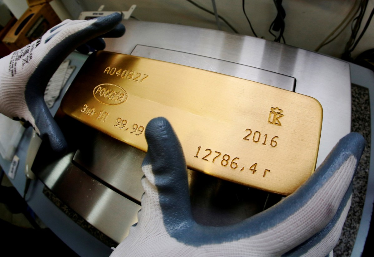 An ingot of 99.99% pure gold sits on the scales in Krasnoyarsk, Russia. Photo: Reuters / Ilya Naymushin