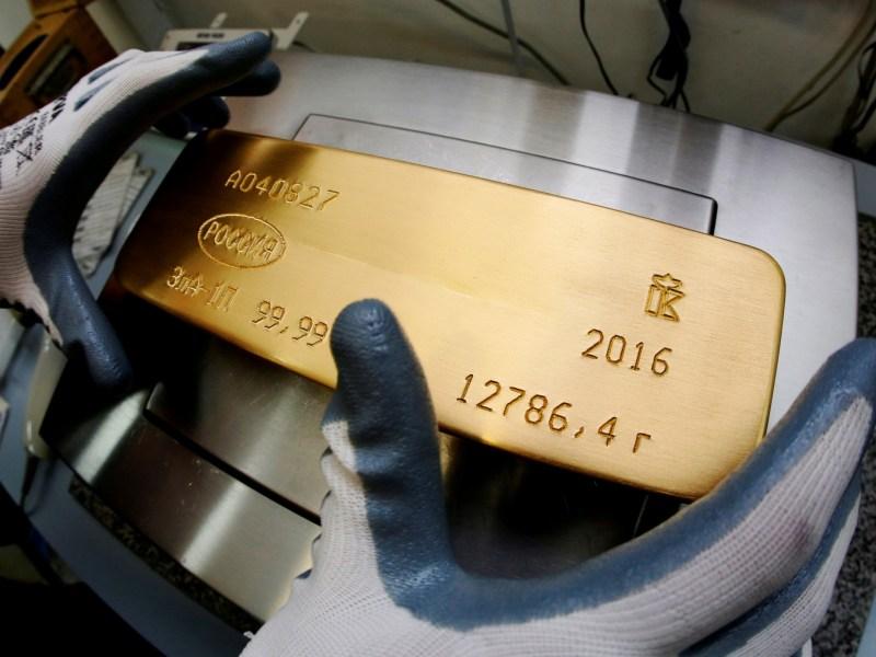 An ingot of 99.99% pure gold sits on the scales in Krasnoyarsk, Russia. Photo: Reuters / Ilya Naymushin