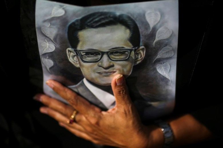 A mourner holds up a picture of Thailand's late King Bhumibol Adulayadej as she wait in line into the throne hall at the Grand Palace to pay respects to his body that is kept in a golden urn in Bangkok, Thailand, November 2, 2016. Photo: Reuters/Athit Perawongmetha
