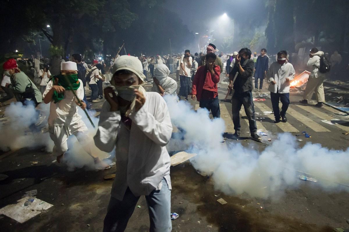Muslim hardline protesters cover their faces as police fire tear gas during a protest against Jakarta's incumbent governor Basuki (Ahok) Tjahaja Purnama on November 4, 2016. Photo: Reuters via Antara Foto/Widodo S Jusuf