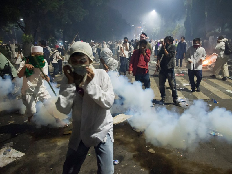 Muslim hardline protesters cover their faces as police fire tear gas during a protest against Jakarta's incumbent governor Basuki (Ahok) Tjahaja Purnama on November 4, 2016. Photo: Reuters via Antara Foto/Widodo S Jusuf