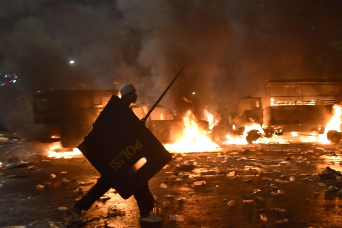 A Muslim protester carries a broken police shield in front of burning trucks during a protest against Jakarta's incumbent governor Basuki (Ahok) Tjahaja Purnama on November 4, 2016. Photo: Reuters via Antara Foto/Wahyu Putro