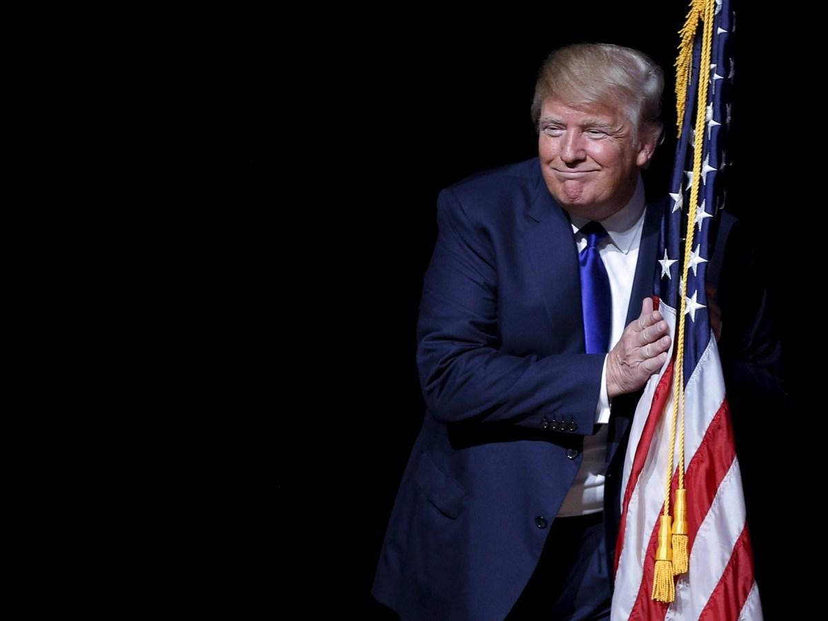 He snuck up on you... Donald Trump hugs a U.S. flag as he takes the stage for a campaign town hall meeting in Derry, New Hampshire. Photo: Reuters/Brian Snyder