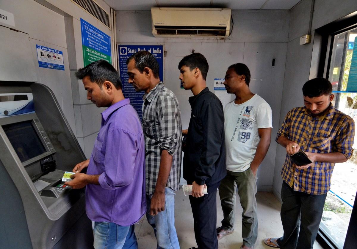 People queue to withdraw and deposit their money at an ATM kiosk in Guwahati, India, November 11, 2016. REUTERS/Anuwar Hazarika
