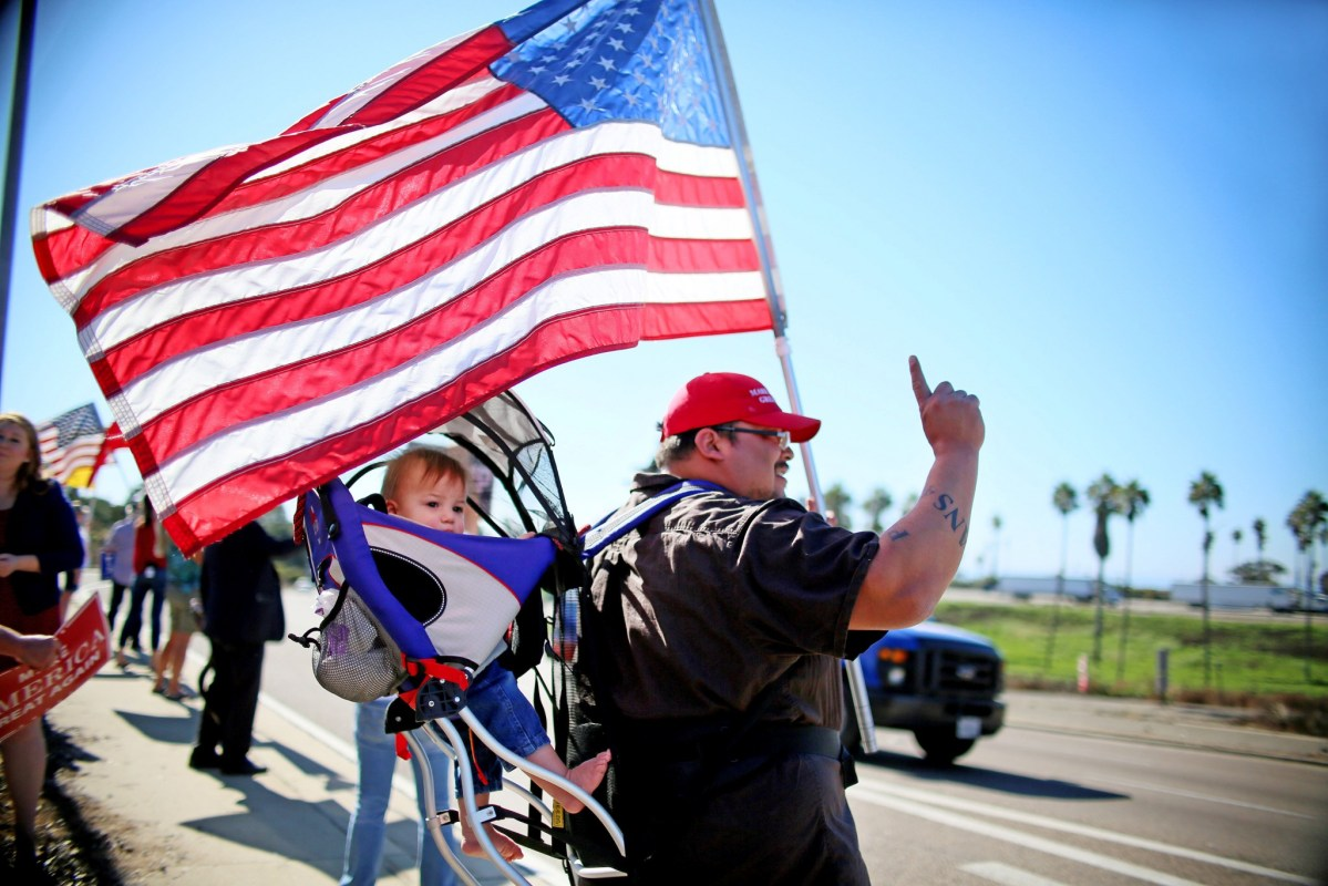 Demonstrator with son waves an American flag in support of President elect Donald Trump in  California, US. Photo: REUTERS/Sandy Huffaker