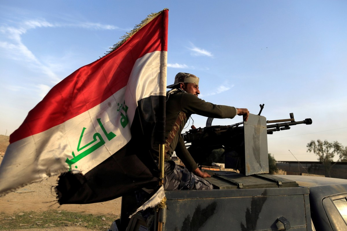 An Iraqi federal policeman aims his heavy machine gun on a vehicle in Samah district, eastern Mosul, Iraq November. Photo: Reuters