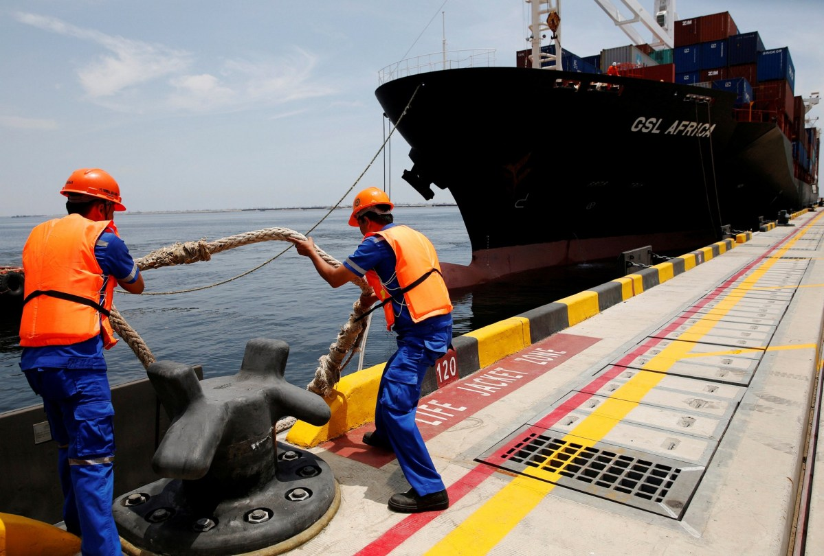 Port workers release the mooring lines to a ship docked at the New Priok Container Terminal 1 in North Jakarta, Indonesia. Photo: REUTERS/Darren Whiteside