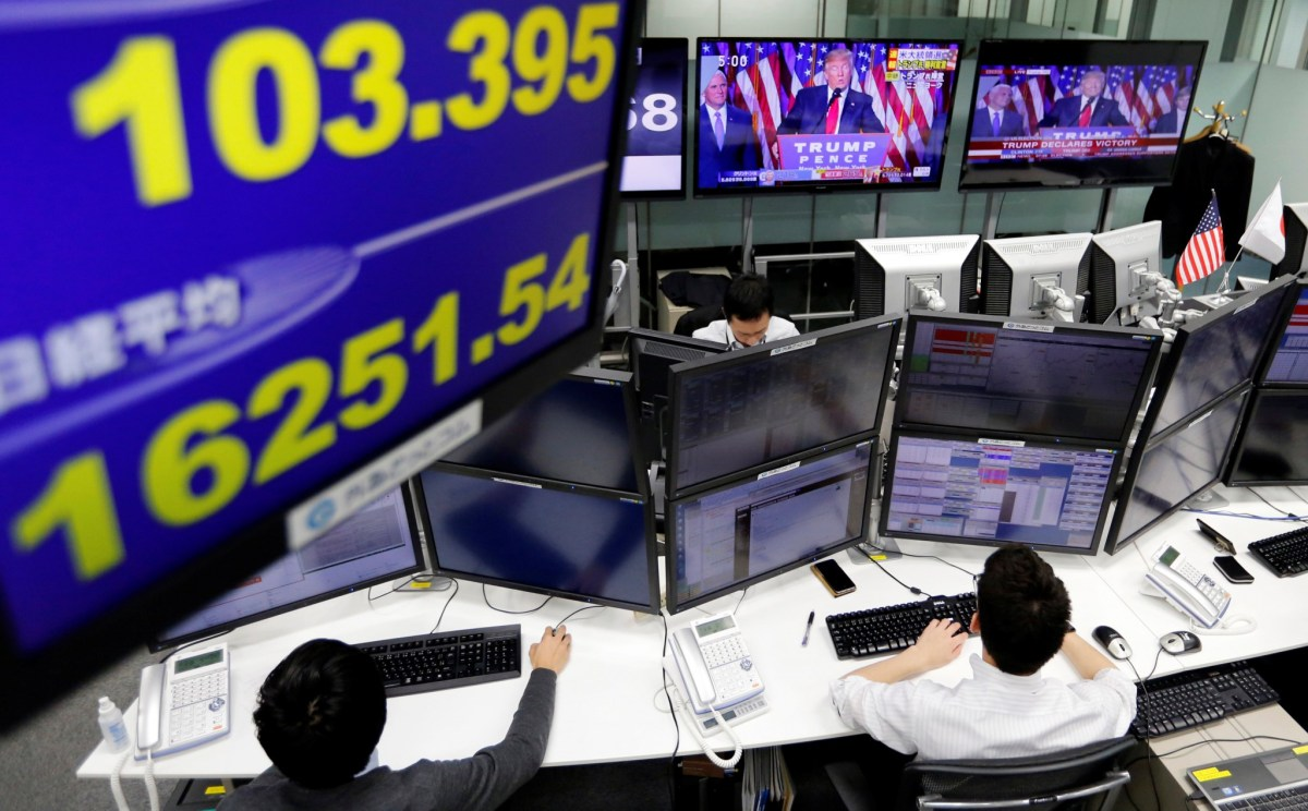 Foreign exchange trading desk, showing  U.S. President elect Donald Trump on TV and the yen's exchange rate against the U.S. dollar (L top) and Japan's Nikkei average in Tokyo, Japan, November 9, 2016. Reuters/Toru Hanai