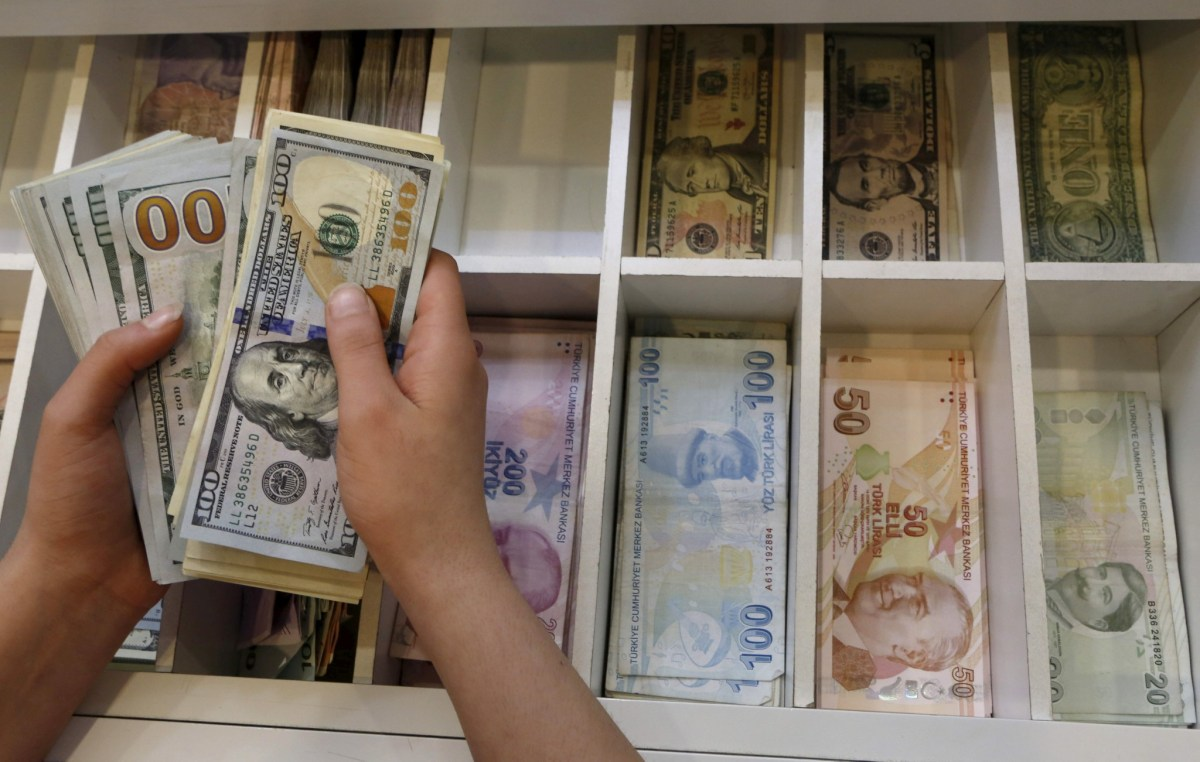 A money changer counts U.S. dollar bills, with Turkish lira banknotes in the background. Photo: Reuters, Murad Sezer