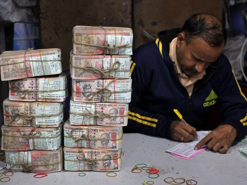 A bank employee fills a form after counting stacks of old 1000 Indian rupee banknotes inside a bank in Jammu, November 25, 2016. Photo: Reuters/Mukesh Gupta