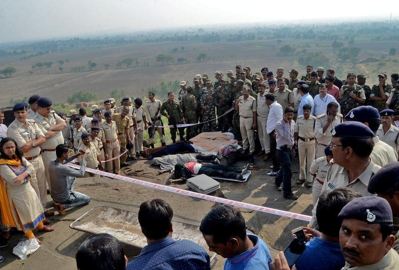 Police officers and Special Task Force soldiers stand beside dead bodies of the suspected members of the banned Students Islamic Movement of India (SIMI), who earlier today escaped the high security jail in Bhopal, and later got killed in an encounter at the Acharpura village on the outskirts of Bhopal, India, October 31, 2016. Photo: Reuters/Raj Patidar