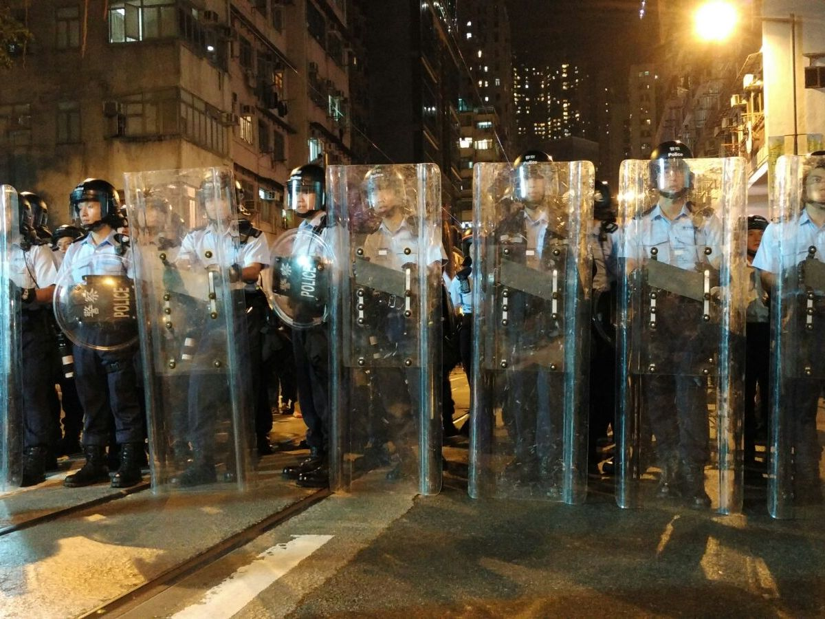 Hong Kong police outside the city's central government liaison office on Sunday night. Photo: Poo Yee-kai