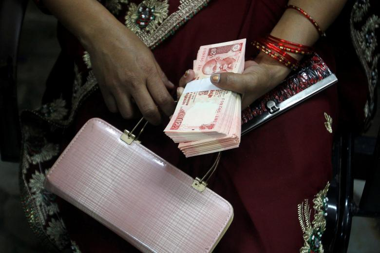 A woman holds Indian banknotes after exchanging them with old high denomination banknotes at a bank in Allahabad. Photo: Reuters/Jitendra Prakash