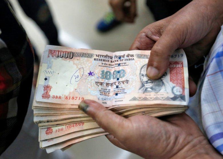 A customer waits to deposit 1000 Indian rupee banknotes in a cash deposit machine in a bank in Mumbai. Photo Reuters/Danish Siddiqui