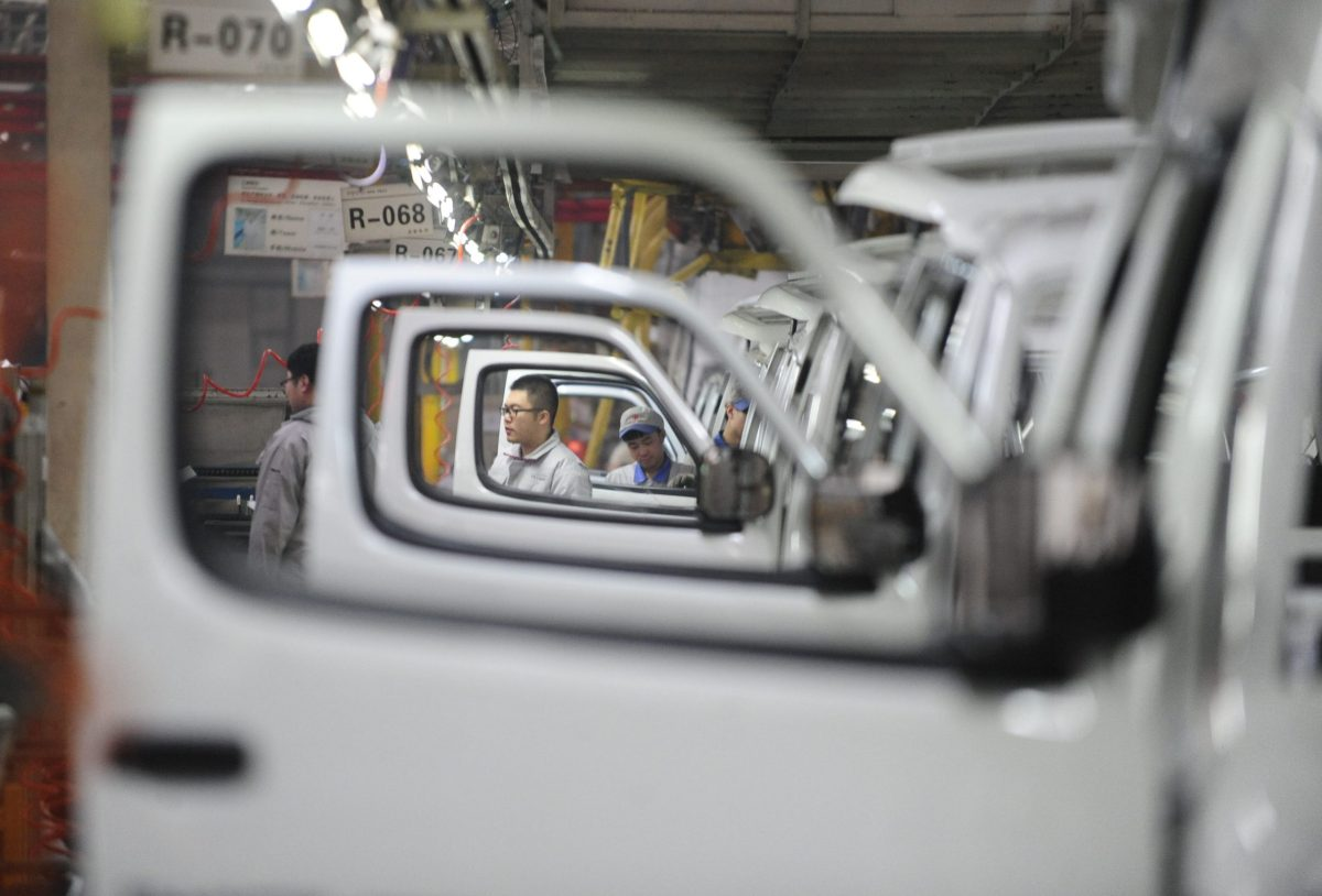 Workers assemble cars at a workshop in Shenyang,  Liaoning province. Photo: AFP