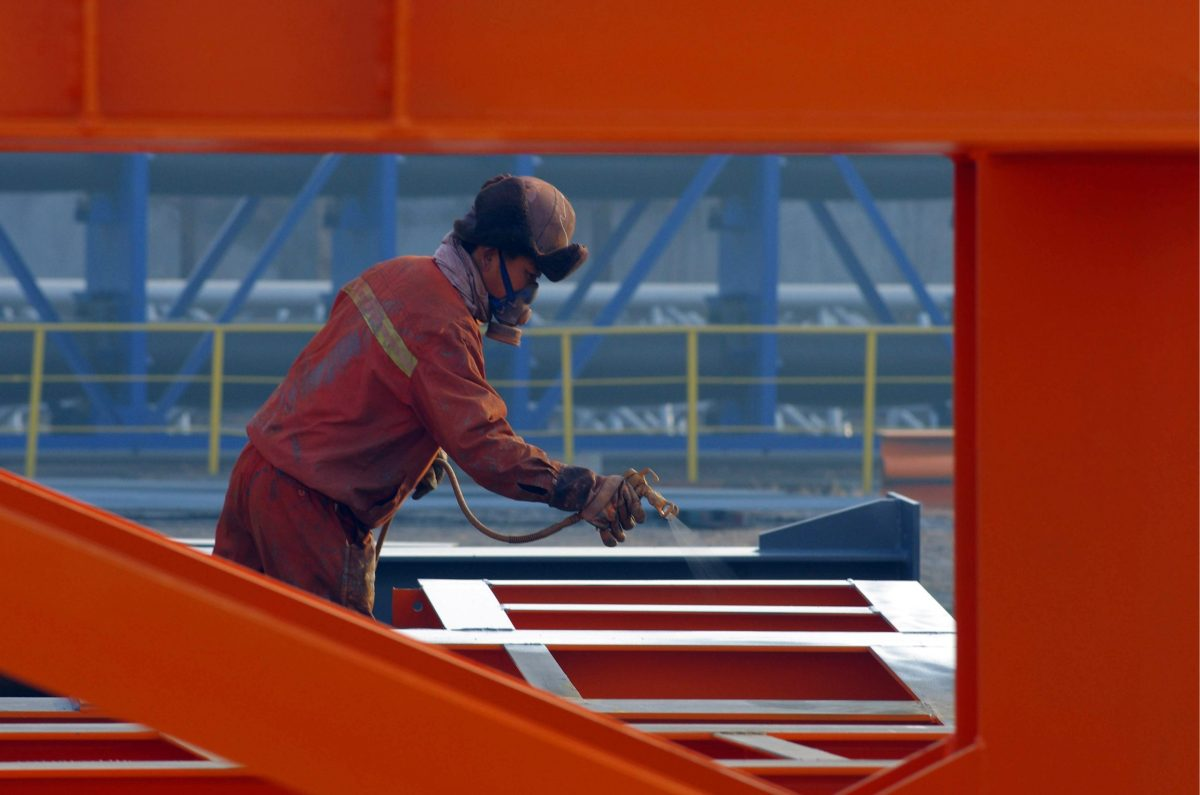 A Chinese worker sprays lacquer on steel in a factory in Rizhao, Shandong province. Photo: Agence-France Presse