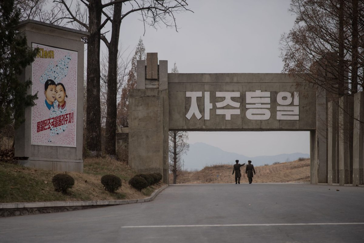 Korean People's Army  soldiers walk past a propaganda painting displayed at the Demilitarized Zone (DMZ) separating North and South Korea, in Panmunjom, near Kaesong, on November 30, 2016. Photo: AFP / Ed Jones