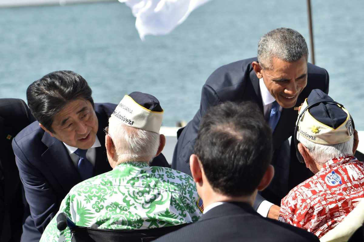 US President Barack Obama (R) and Japanese Prime Minister Shinzo Abe greet veterans at Kilo Pier overlooking the USS Arizona Memorial on December 27, 2016 at Pearl Harbor in Honolulu, Hawaii. Photo: AFP/Nicholas Kamm